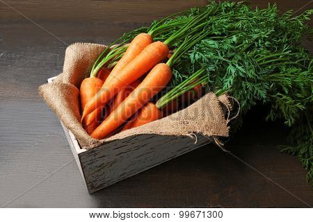 Fresh organic carrots in box with sackcloth on wooden background