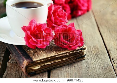 Old book with beautiful roses and cup of coffee on wooden table close up