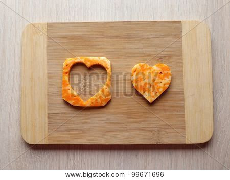 Cheese slice with cut in shape of heart on wooden background
