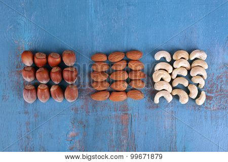 Dried fruits and nuts on color wooden background