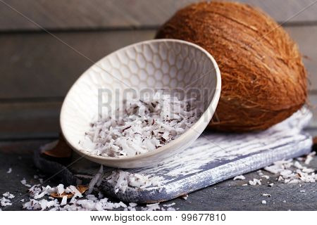 Coconut shavings in bowl with coconut on wooden background