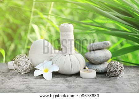 Spa still life on wooden surface over green reeds on river