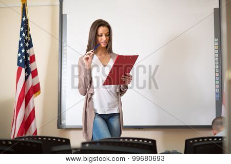 Young beautiful and attractive teacher preparing for lecture in classroom