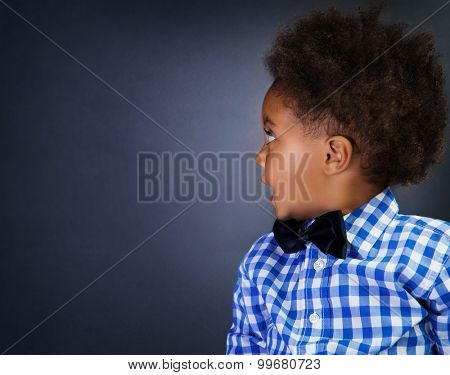 Portrait of cute little African schoolboy with surprise looking in side, over blackboard background, copy space, back to school