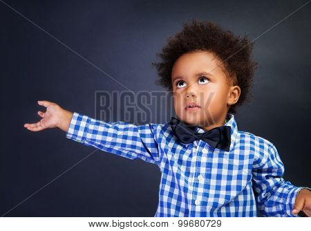 Cute little boy portrait, adorable African schoolchild over blackboard background, copy space, elementary school, start of educational season