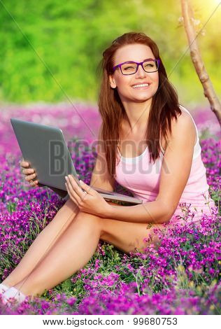 Cheerful student girl in the park, sitting on flower meadow and doing homework on laptop, studying in high school, back to school