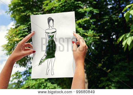 Female hands holding fashion sketch outdoors