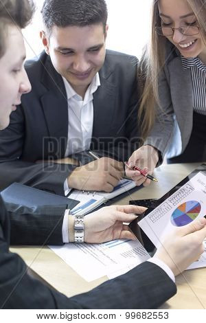 Smiling female manager explains corporate data to her associate
