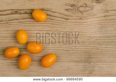 Oval Kumquats On Old Spruce Wood Board