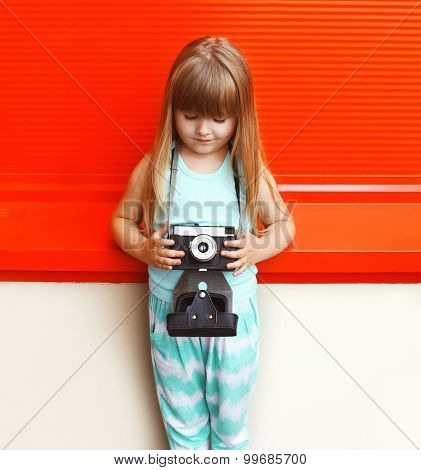 Fashion Kid Concept - Little Girl Child With Old Retro Vintage Camera Against The Colorful Red Wall