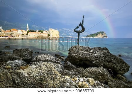 The Statue Of A Dancing Girl On A Background Of The Old Town Of Budva