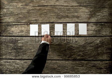 Top View Of Businessman Hand Placing Five Blank White Peaces Of Paper Or Cards On Textured Rustic Wo
