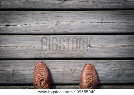 Man feet in shoes  on the wood floring.