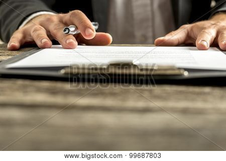 Closeup Of Male Hand About To Sign A Subscription Or Application Papers