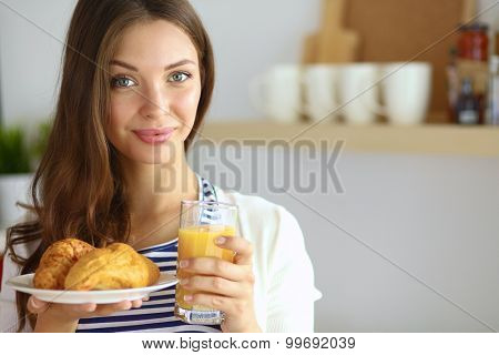 Young woman with glass of juice and cakes