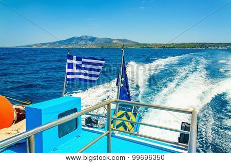 Wake from Greek speed boat and Greece flag