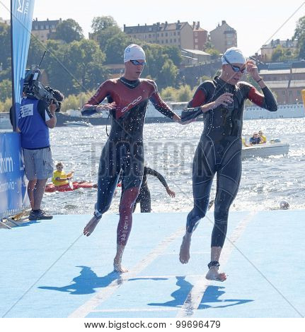 Two Female Swimmer Climbing Up From The Water