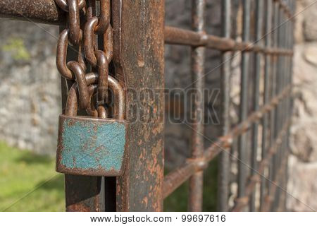 The lock on the chain. Old rusty chain with a lock on the iron gate.