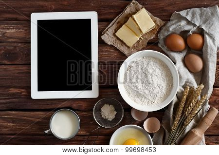 White tablet computer with blank screen with ingredients for making pancakes or cake