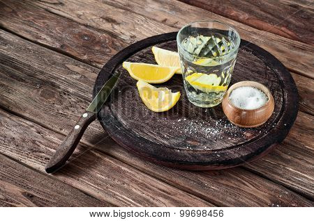 glass of tequila with lemon slices and salt on a wooden circular board