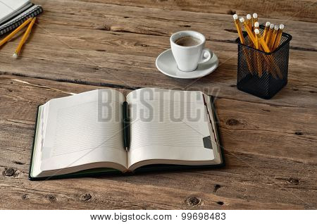 on the wooden table lies a open diary for entries with a cup of coffee and pencils