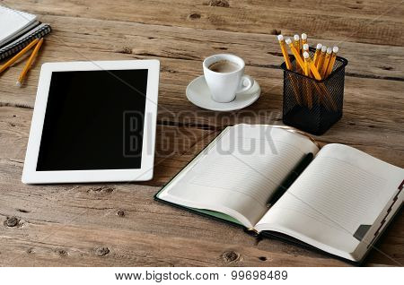 Tablet computer on the wooden desk with an open notepads, pencils and cup of coffee closeup