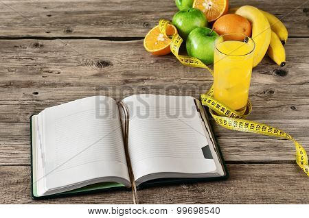 Open notebook for notes of fruit (apple, orange, banana) and orange juice on a wooden table