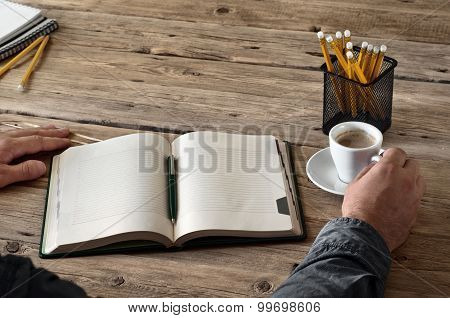 man holding a cup of coffee over an open diary notes closeup
