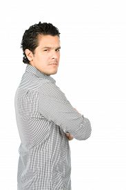 stock photo of disappointed  - Rear view of angry disappointed latino man wearning casual clothes arms crossed looking behind at camera over his shoulder showing judgmental critical unhappy displeased attitude - JPG