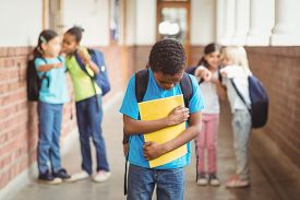 image of school bullying  - Sad pupil being bullied by classmates at corridor in school - JPG