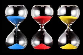 picture of pass-time  - Three hourglasses with colorful sand blue red and yellowrunning through the glass bulbs measuring the passing time or time remaining to a deadline over a black background - JPG