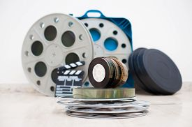 image of mm  - Heap of old 35 mm movie reels with out of focus clapper and boxes in background - JPG
