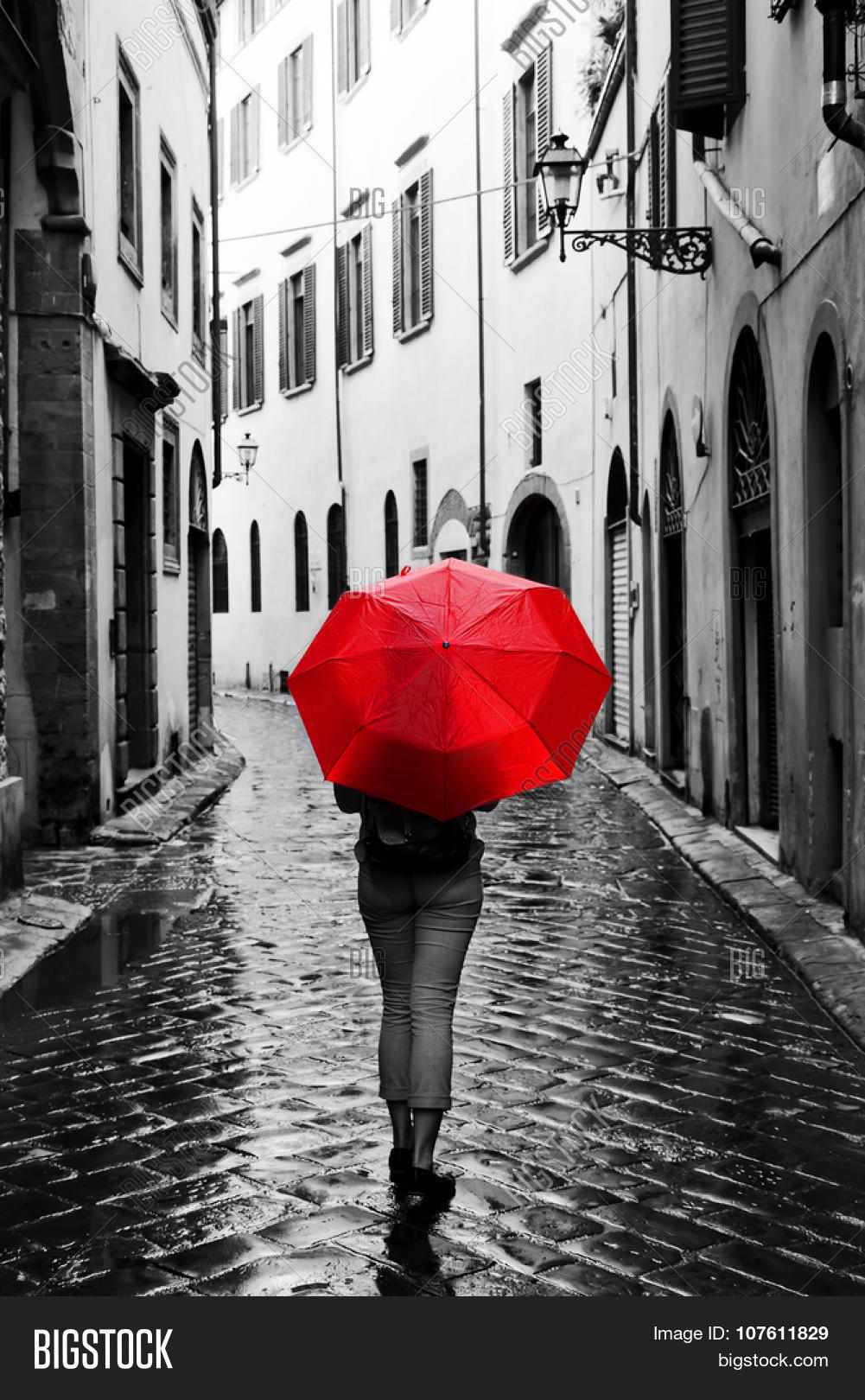 woman with red umbrella on cobblestone street in the old