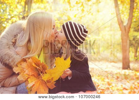 Happy daughter kissing her mother in autumn park and play collects a bouquet of yellow maple leaves.