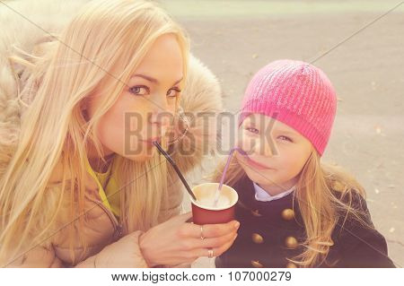 Cute young mother with daughter have a fun drinking a milkshake from the same paper cup using a tubes.