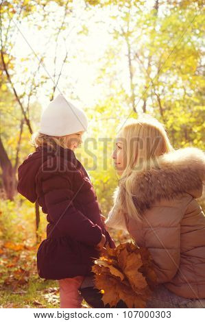 Small daughter and her mother looking at each other and smiling, happy childhood, sunny backlight in autumn park.