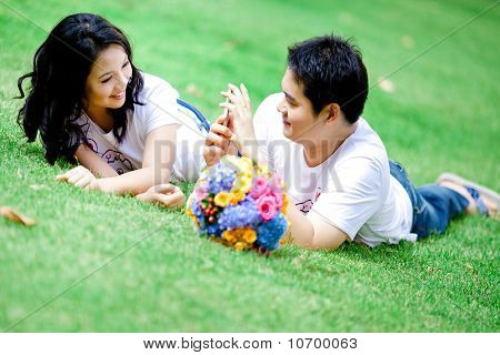 Young Boy Taking Her Girlfriend Photo With His Mobile Phone On Grass