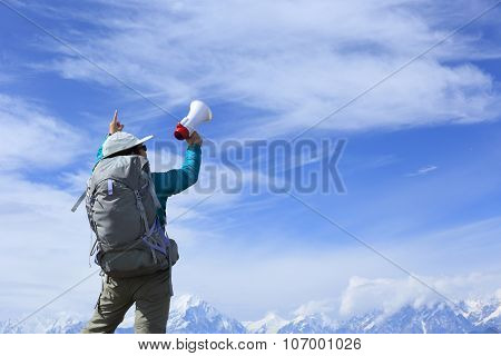 young woman backpacker shouting with loudspeaker