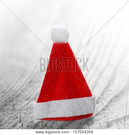 Small decorative Santa Claus hat on wooden background