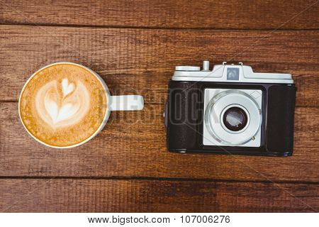 View of an old camera with coffee on wood desk