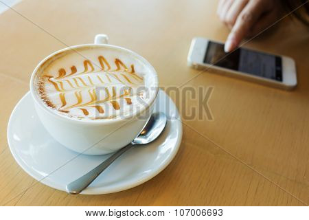 Hot Of Coffee Drink On Wooden Table Bar With Mobile Phone In The Cafe