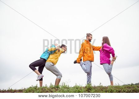 Friends stretching before a hike in the countryside