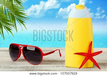 Bottle of suntan cream with sunglasses and sea star on table on water background