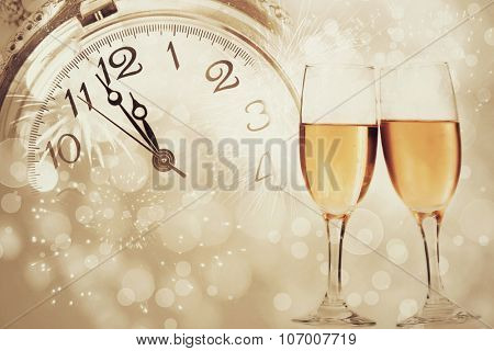 Glasses with champagne against fireworks and clock close to midnight