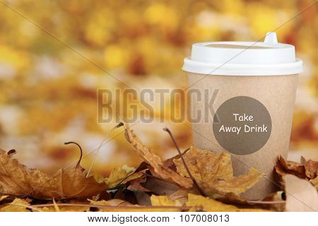 Hot drink in paper cup with yellow leaves on bright autumn background