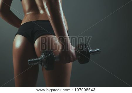 Young Woman Back Training With Dumb-bell Against Gray Background