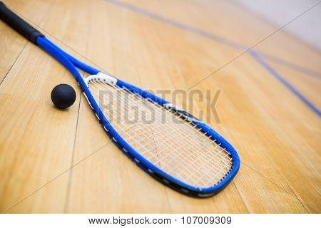 Close up of a squash racket and ball in the squash court