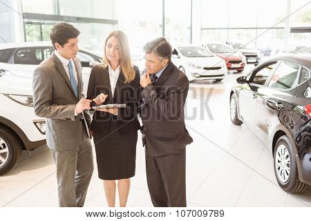 Sales team look at a clipboard at new car showroom