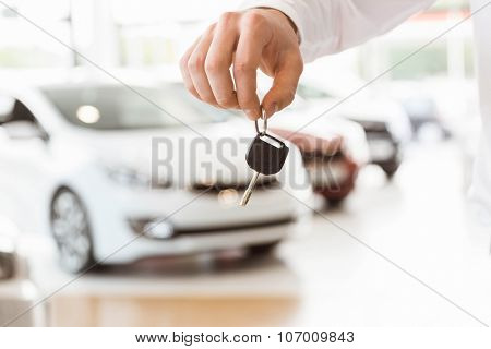 Someone holding car keys by his fingertips at car showroom