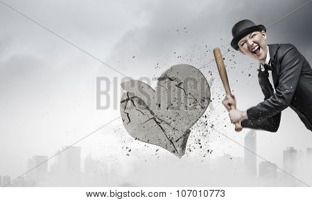 Young emotional woman in suit and hat with baseball bat
